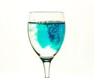 Ein Glas/Glas mit klarem Wasser wird mit einer blauen Flüssigkeit gefüllt Lizenzfreie Stockfotos