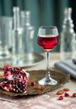 Ein Glas Granatapfellikör auf dem Tisch mit Granaten stockfoto
