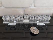 Ein Glas-Hannuka und ein silbernes dreidel auf einem schwarzen Klavier mit Steinwand im Hintergrund Stockfotografie