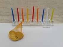 Ein Glas-Hannukiah füllte mit bunten Kerzen auf einer weißen Tabelle mit einem Säckchen chocholate Münzen Lizenzfreie Stockfotografie