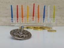 Ein Glas-Hannukiah füllte mit bunten Kerzen auf einer weißen Tabelle mit einigen zerstreuten chocholate Münzen und einem silberne Lizenzfreie Stockfotografie