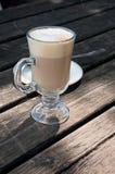 Ein Glas heißes latte macchiato auf einer hölzernen Tabelle stockfotografie