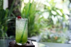 Ein Glas italienisches Soda der Kiwi auf einer hölzernen Untertasse im Café lizenzfreie stockfotografie
