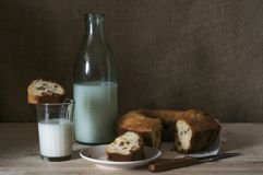 Ein Glas Milch mit einem kleinen Kuchen Lizenzfreie Stockbilder