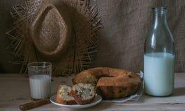 Ein Glas Milch mit einem kleinen Kuchen Stockbilder