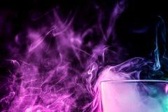 Ein Glas mit buntem Rauche Stockfotografie