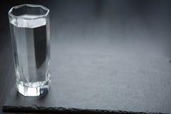 Ein Glas mit Wasser im dunklen Hintergrund lizenzfreie stockfotos