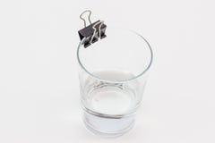 Ein Glas mit wenigen Wasser in ihm und einem Mappenclip auf ihm ` s Kante Stockbilder
