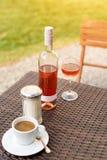 Ein Glas und Flasche roter oder rosafarbener Wein im Weinberg mit Tasse Kaffee Erntezeit, Café oder Picknick, Festthema Stockfotografie