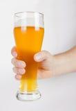 Ein Glas ungefiltertes Bier in der Hand auf Weiß Stockbilder