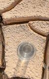 Ein Glas Wasser auf ausgetrocknetem Boden II Stockfotografie