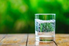 Ein Glas Wasser auf grünem Hintergrund Lizenzfreie Stockfotos