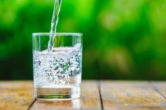 Ein Glas Wasser auf grünem Hintergrund Stockbild