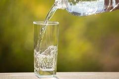Ein Glas Wasser gießt in das Glas, auf der Natur Stockfoto