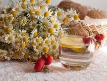 Ein Glas Wasser mit einer Zitronenscheibe in ihr, ein Blumenstrauß der Kamille und eine Platte von reifen Pflaumen auf einer Spit Stockbild