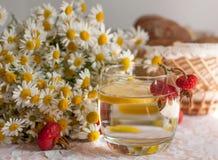 Ein Glas Wasser mit einer Zitronenscheibe in ihr und ein Blumenstrauß der Kamille auf einer Spitzeoberfläche verziert mit Hüften Lizenzfreie Stockfotografie
