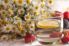 Ein Glas Wasser mit einer Zitronenscheibe in ihr und ein Blumenstrauß der Kamille auf einer Spitzeoberfläche verziert mit Hüften Stockfotos