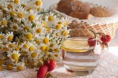 Ein Glas Wasser mit einer Zitronenscheibe in ihr und ein Blumenstrauß der Kamille auf einer Spitzeoberfläche verziert mit Hüften Lizenzfreie Stockfotos