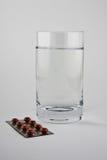 Ein Glas Wasser und Pillen Lizenzfreies Stockbild