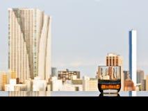 Ein Glas Whisky mit panoramischer Stadtansicht Stockfotografie