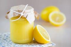Ein Glas Zitronenklumpen mit einer Zitrone Lizenzfreie Stockfotos