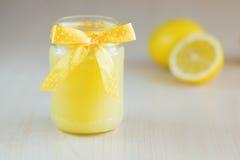 Ein Glas Zitronenklumpen mit einer Zitrone Stockbilder