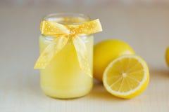 Ein Glas Zitronenklumpen mit einer Zitrone Lizenzfreies Stockbild