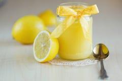 Ein Glas Zitronenklumpen mit einer Zitrone Lizenzfreie Stockbilder