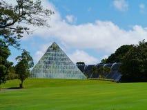 Ein Glashaus mit Palmen in einem Park Stockbild