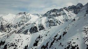 Ein glatter Flug über den schneebedeckten Bergen mit Tannen Winterlandschaft mit Blick auf steinige Berge im Schnee und Himmel in stock footage