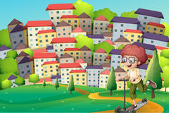Ein glücklicher Junge, der mit einem Roller an den Hügeln spielt Stockbilder
