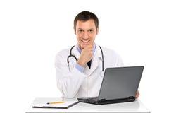 Ein glücklicher junger Doktor, der an einem Laptop arbeitet Lizenzfreie Stockfotografie