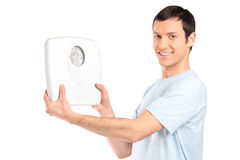 Ein glücklicher junger Mann, der eine Gewichtskala anhält Lizenzfreie Stockfotos