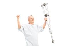 Ein glücklicher reifer Patient, der Krücken hält und Glück gestikuliert Stockbild