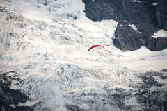 Ein Gleitschirmfliegen ist über dem Gletscher lizenzfreie stockfotos