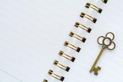 Ein Goldmetallschlüssel auf Weißbuch Stockbilder