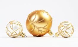 Ein Goldweihnachtsball und zwei weißes Weihnachtsbälle Stockfoto