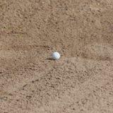 Ein Golfball in einem Sandfang Lizenzfreies Stockfoto