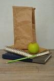 Ein grüner Apfel eine Papiermittagessentasche und ein Stapel Bücher Lizenzfreie Stockfotografie