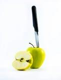Ein grüner Apfel und ein halber Apfel mit Messer auf einem weißen Hintergrund Stockbilder