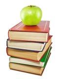 Ein grüner Apfel und ein Stapel alte Bücher Stockbild