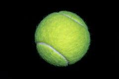 Ein grüner Tennisball lokalisiert auf schwarzem Hintergrund Stockbild