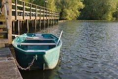 Ein grünes Boot mit Rudern auf dem See an einer hölzernen Birne im Sommer nahe dem Wald Stockfotografie