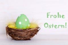 Ein grünes Osterei im Nest mit Deutschem Frohe Ostern bedeutet fröhliche Ostern Stockfotografie