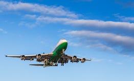 Ein Grünes und ein Weiß 747 landend an internationalem Flughafen Vancouvers an einem sonnigen Tag stockbild
