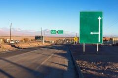 Ein grünes Verkehrsschild steht nahe bei einer Straße in der atacama Wüste mit einem Pfeil, der steigt und einer rechts Lizenzfreies Stockfoto