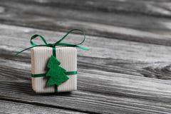 Ein grünes Weihnachtsgeschenk auf hölzernem grauem Hintergrund Stockfotografie
