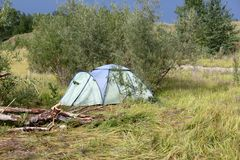 Ein grünes Zelt auf einem Picknick in einem Wald auf einem Sand mit Gras Lizenzfreie Stockfotos