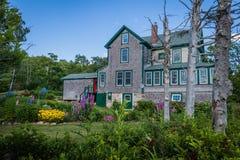 Ein Grau und ein umweltgerechtes Haus mit heller roter Tür ist ein Neu-England Arthaus in Küsten-Maine Lizenzfreies Stockfoto