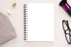 Ein grauer Hut, eine Anmerkung, parfums, eine Bürste und Gläser auf grauem Hintergrund stockbilder